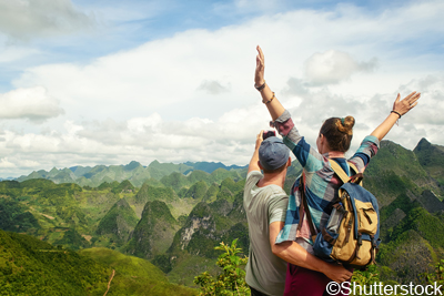 Couple of tourists making selfie on the background of beautiful karst mountains, North Vietnam. Mountains and landscape, travel to Asia, happiness emotion, summer holiday concept.